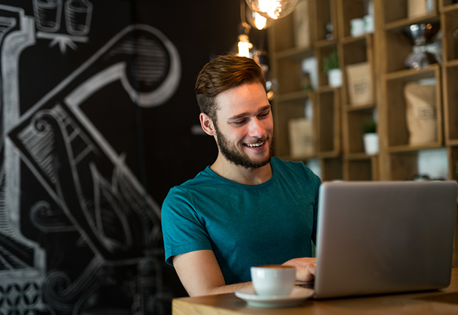 A young professional working on his laptop while having a coffee in a coffee shop