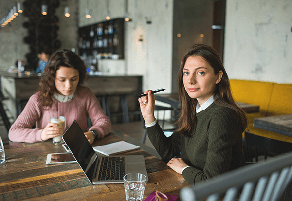Two woman working at a coffee shop with their laptop. One looking at the camera.